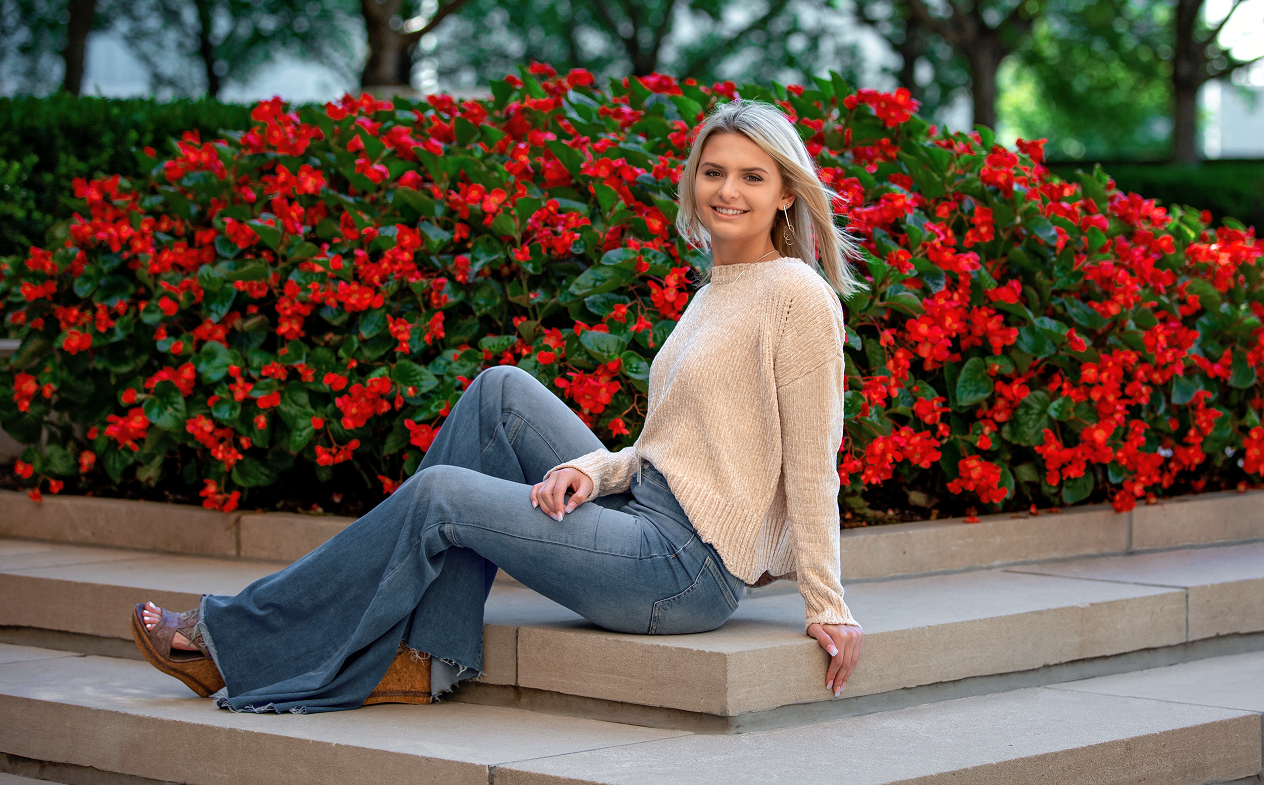 A young blonde girl wearing bell-bottom jeans and a pink sweater sitting three-quarter profile to the camera on a small set of stairs with vibrant red flowers in the background.