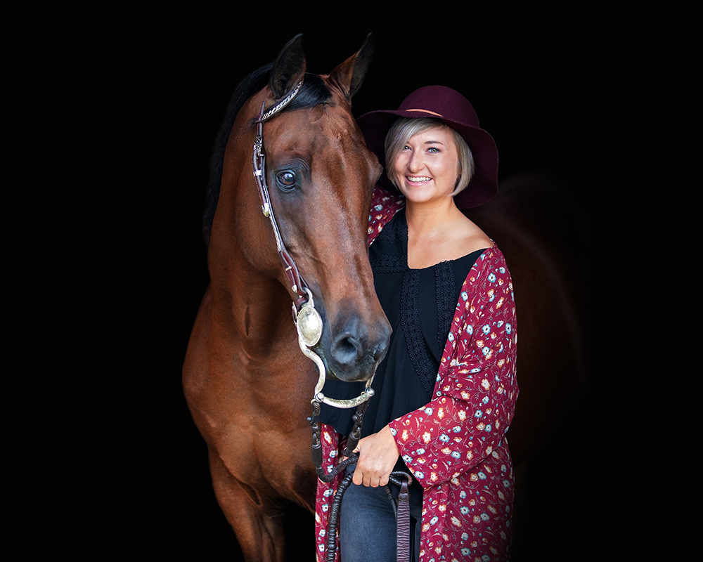 A headshot of a young woman and her bright bay horse on a black background.