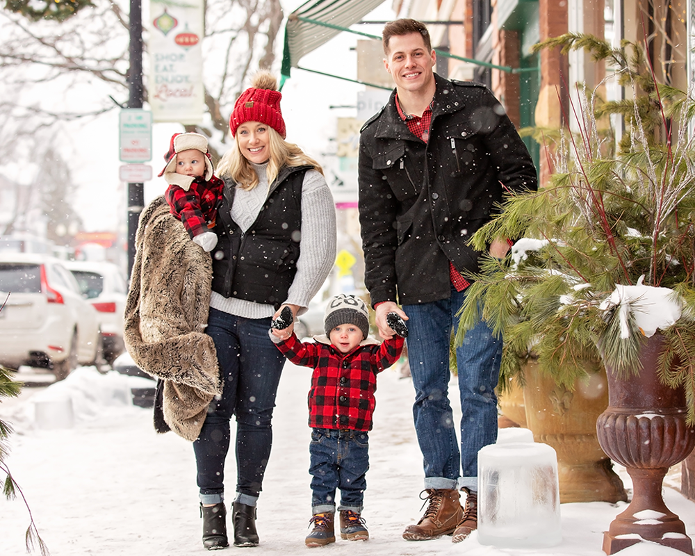 A young family walking down the streets of a busy Minnesota town in the winter wearing buffalo checked clothing.