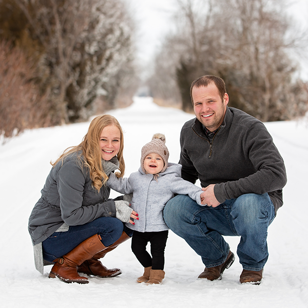 A young couple with their toddler kneeling on a snow covered path.