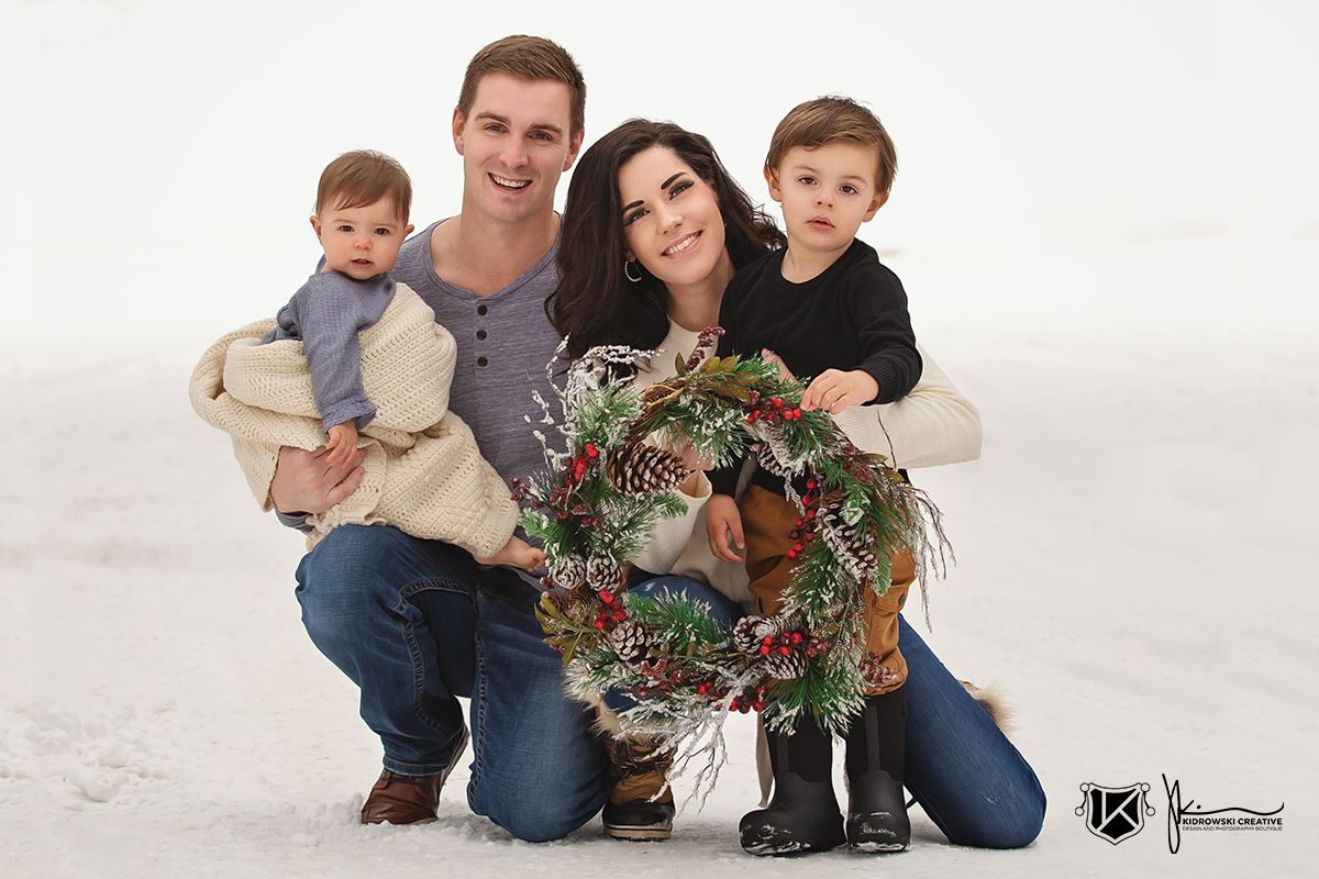 Gorgeous winter family photography with a family of four. Young parents with a toddler and an infant holding a Christmas wreath in the snow.