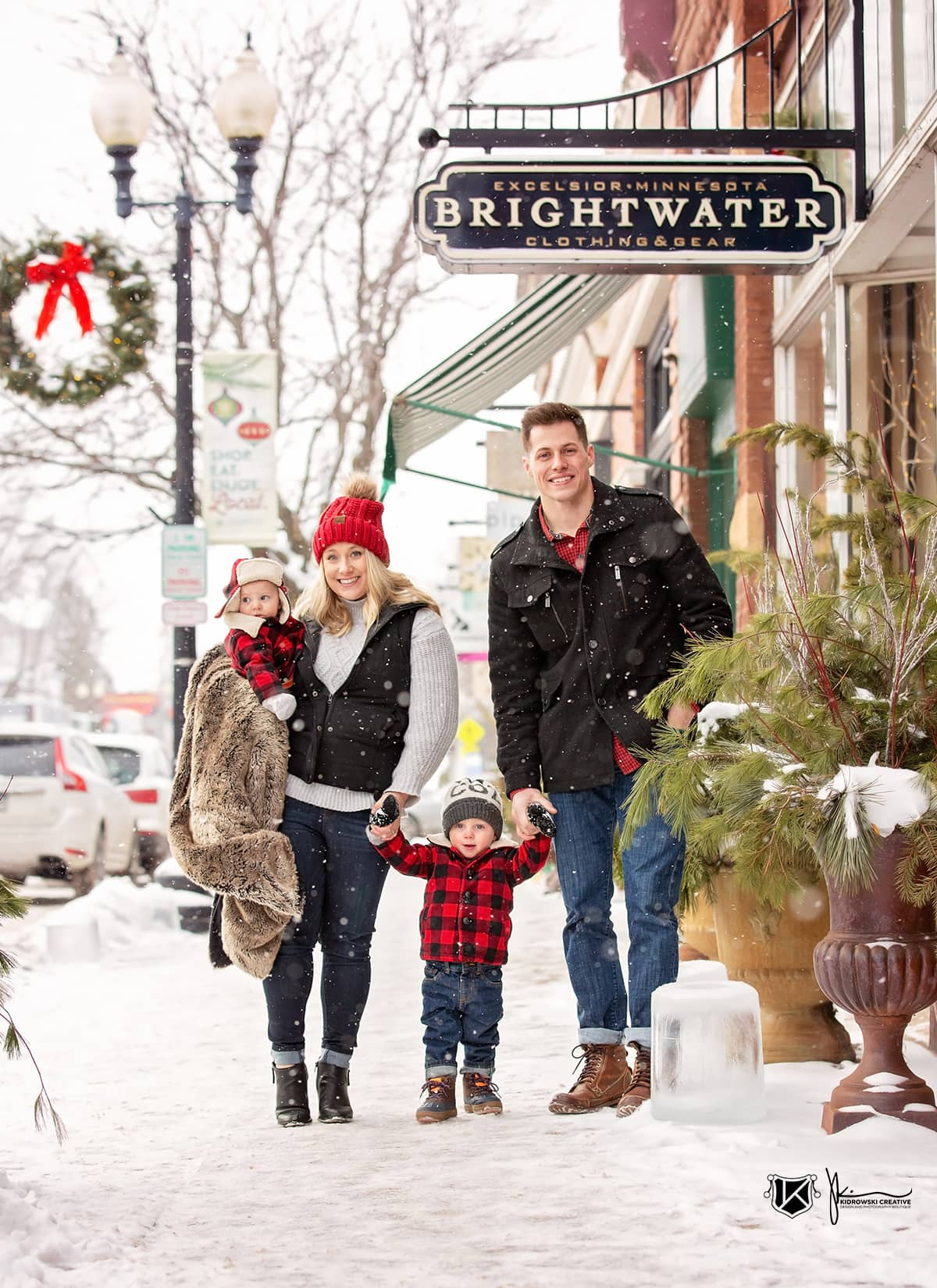 Young family walking the streets of Excelsior, Minnesota during a winter snowstorm at Christmas time.