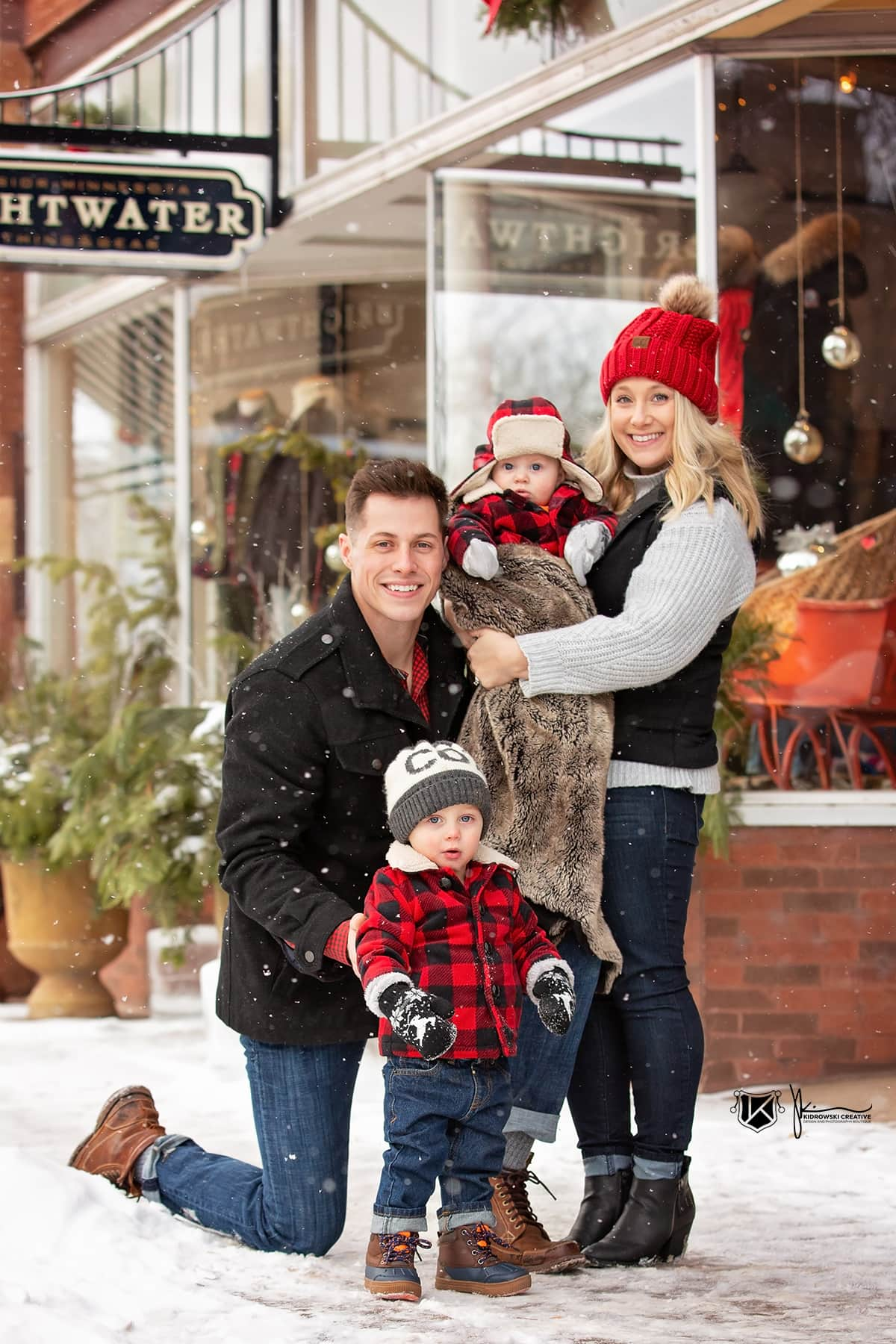 Young family of four huddled together and smiling at the camera near a small shop in central Minnesota.