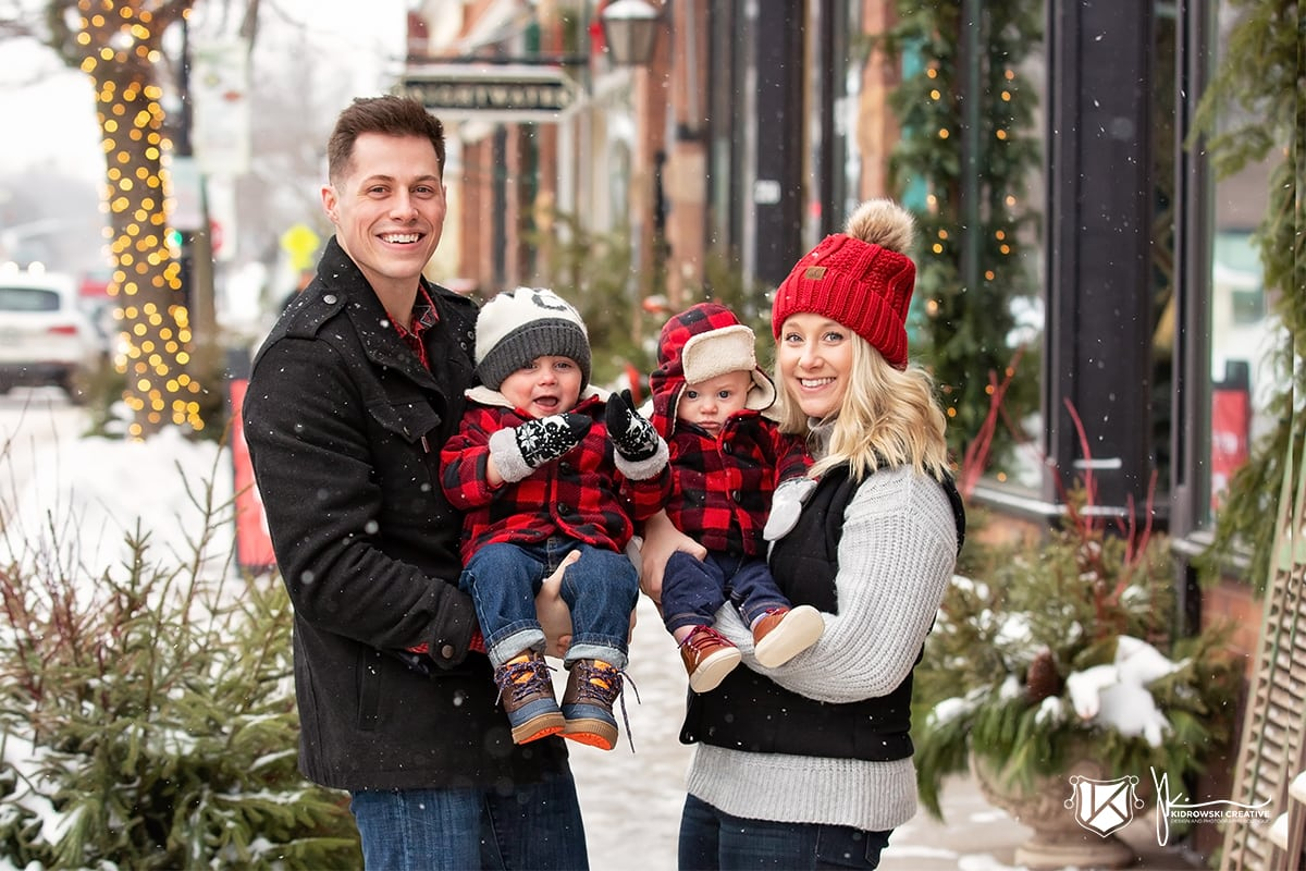 Young family of four dressed in matching flannel smiling at the camera with Christmas lights in the background.