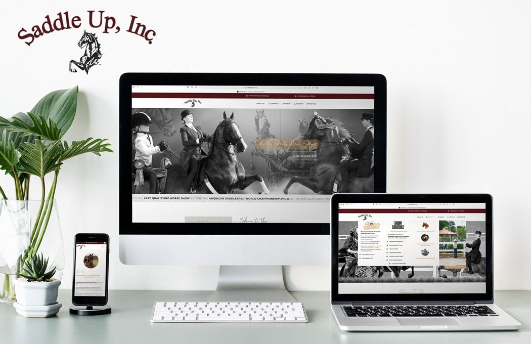 A computer monitor, laptop and cell phone all displaying the home page of Saddle Up, Inc. and the Longview Charity Horse Show website.
